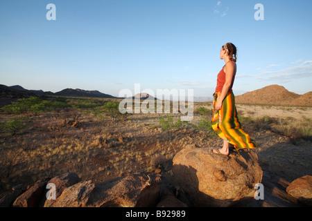 Woman standing on rock overlooking the Marienfluss Red Drum Kaokoland Namibia - Stock Photo