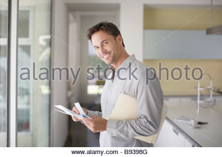 Man sorting mail at home - Stock Photo