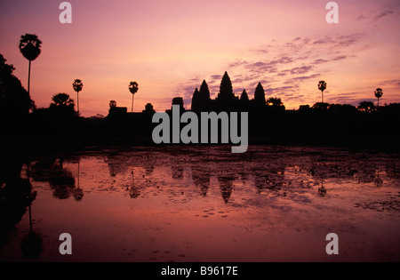 CAMBODIA Siem Reap Angkor Wat Central temple complex seen in silhouette across and reflected in the water lily pond - Stock Photo