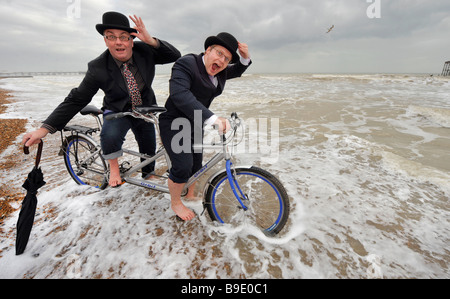 City gents limber up on Brighton beach with their tandem before competing in 'The Rat Race' event . - Stock Photo