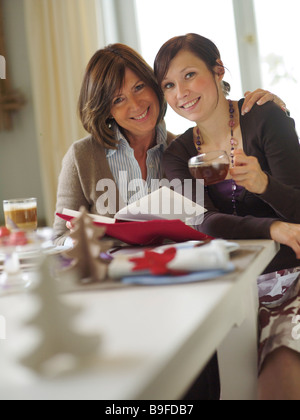 Portrait of woman and her daughter smiling at table - Stock Photo
