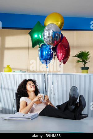 Young woman with balloons in office - Stock Photo
