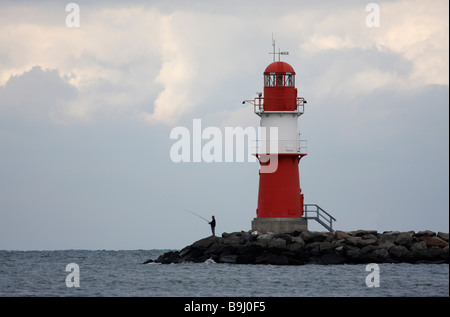 Man fishing at a lighthouse on the coast of the Baltic Sea, Warnemuende, Mecklenburg-Western Pomerania, Germany, - Stock Photo