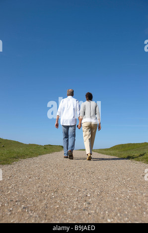 Mature couple walking away together - Stock Photo
