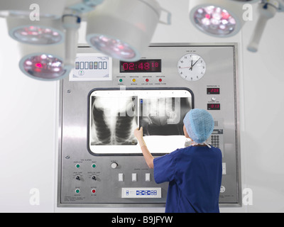 Nurse with x-rays in operating theatre - Stock Photo