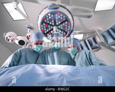 Group of surgeons operating in theatre - Stock Photo