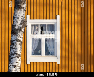 White framed window on yellow plank wall , Finland - Stock Photo