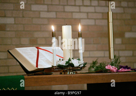 Candles and a bible on an altar - Stock Photo
