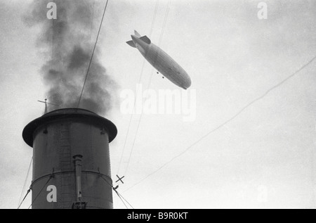 The German airship Earl Zeppelin floating in the air above the Malygin polar vessel funnel - Stock Photo