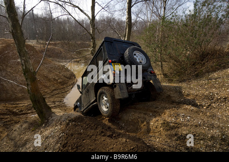 A Land Rover Defender 90 driving down a steep bank during an Off Road exercise - Stock Photo