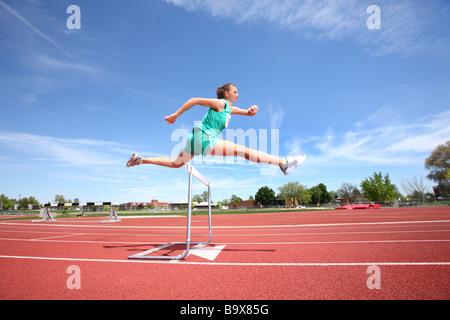 Woman jumping over hurdle - Stock Photo