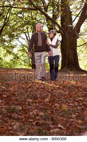 A senior couple walking through autumn leaves - Stock Photo