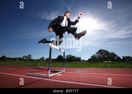 Businessman jumping over track hurdle - Stock Photo