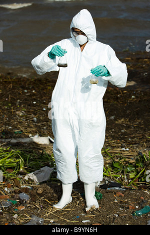 Person in protective suit holding up flasks filled with polluted water - Stock Photo