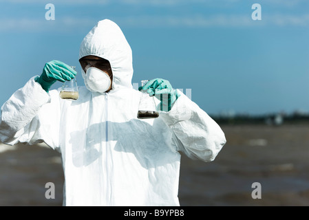 Person in protective suit holding flasks filled with polluted water - Stock Photo