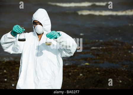 Person in protective suit testing polluted water - Stock Photo