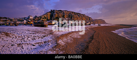 A winter snow snow scene of the East Hill and Fishing boats on the Stade beach  Hastings. East Sussex - Stock Photo