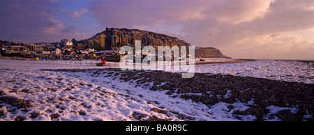 A winter snow snow scene of the East Hill and Fishing boats on the Stade beach  Hastings. East Sussex. - Stock Photo