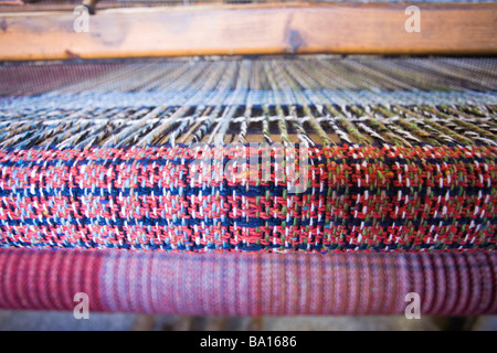 Loose Woven Tweed on the Loom. A red, blue and green tweed being woven on a a hand loom. - Stock Photo