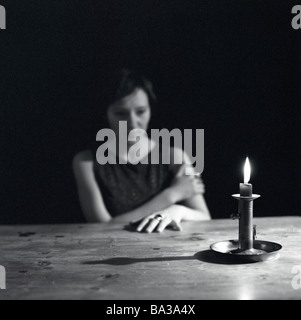 Sits woman table candle burns semi-portrait fuzziness s/w people young gaze expression seriously silence lowered - Stock Photo