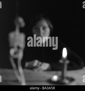 Sits woman table candle burns skeleton views fuzziness s/w people young expression seriously silence silence meditation - Stock Photo