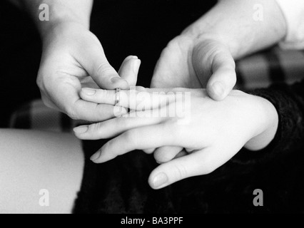 Seventies, black and white photo, betrothment, marriage, symbolic, hands, man places an engagement ring on womans - Stock Photo