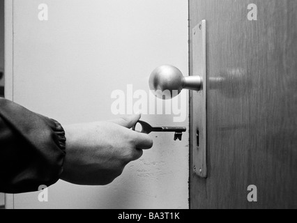 Seventies, black and white photo, symbolic, safety, open up an apartment door, hand holding a key, doorknob - Stock Photo