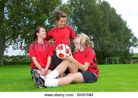 Teenage girls in soccer uniforms sitting on field - Stock Photo