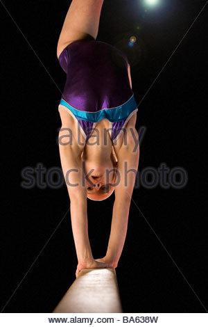 Young female (10-12) gymnast performing on balance beam, low angle view (lens flare) - Stock Photo