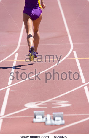 Female athlete running on race track - Stock Photo