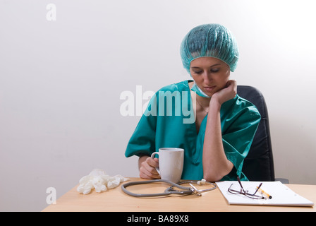 Tired doctor sat in office drinking coffee - Stock Photo