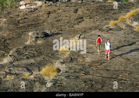Tourists hike up the escarpment to the Nadab lookout at Ubirr.  Kakadu National Park, Northern Territory, AUSTRALIA - Stock Photo