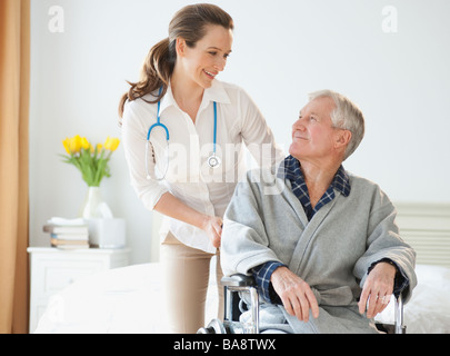 Nurse helping senior man in wheelchair - Stock Photo