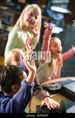 Elementary school kids with arms raised at computer in library - Stock Photo