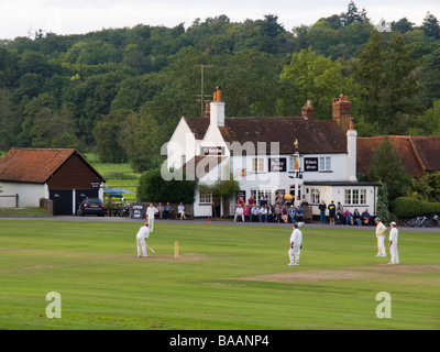 Playing cricket on a village green outside the Barley Mow country pub in summer. Tilford Surrey England UK Britain - Stock Photo