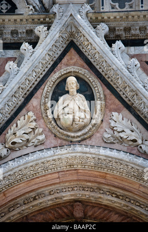 Carved marble figures on the facade of the Duomo (cathedral) seen from Piazza del Duomo, Siena, Tuscany, Italy. - Stock Photo