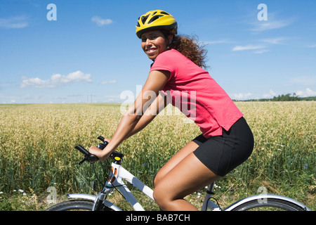 A woman riding a bike in the countryside, Sweden. - Stock Photo