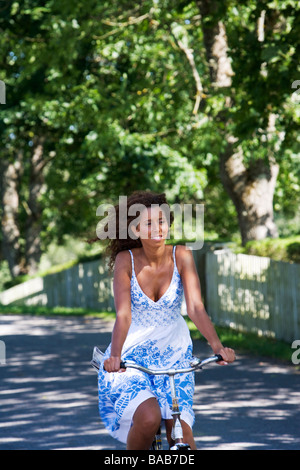 A woman riding a bike in the Swedish countryside. - Stock Photo