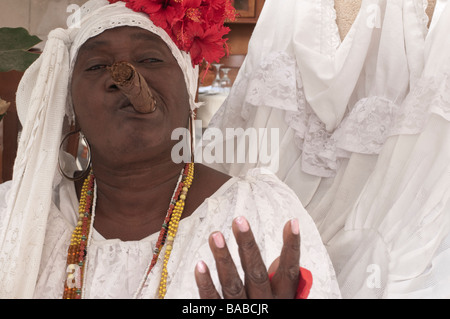 Woman smoking a large cigar in Havana Vieja with a white and floral headdress. - Stock Photo