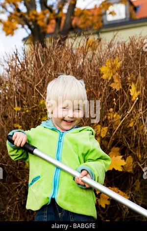 A little boy raking leaves in the garden Sweden - Stock Photo