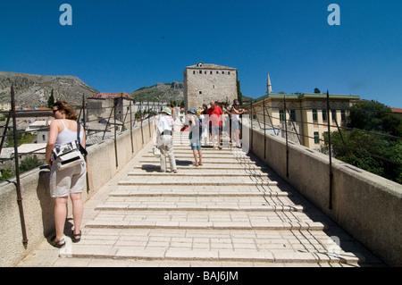 Tourists on famous Stari Most old bridge over Neretva River Mostar Bosnia Eastern Europe - Stock Photo