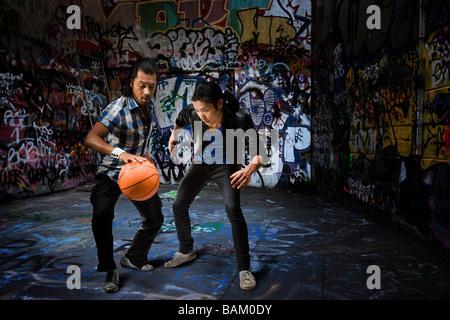 Two men playing basketball - Stock Photo