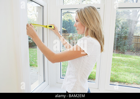 Young woman measuring a window - Stock Photo