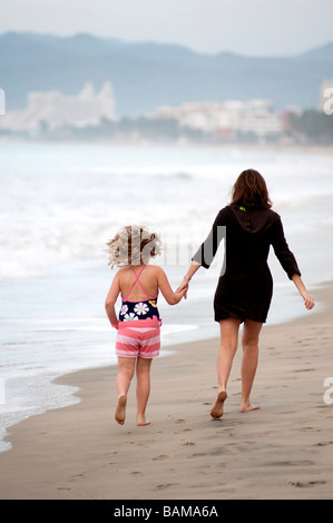 Mother and daughter walking on the beach; Puerto Vallarta, Mexico; - Stock Photo