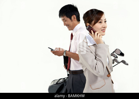 Businessman And Businesswoman With Golfclubs - Stock Photo