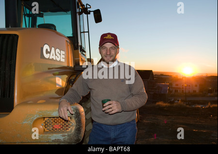 Early morning portrait of small business owner and front end loader operator on a construction site - Stock Photo
