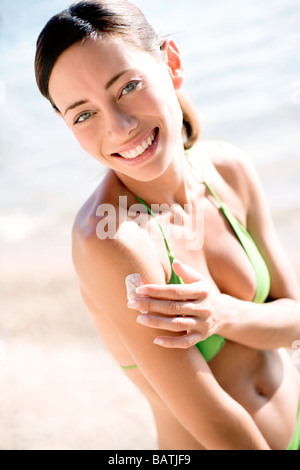 Woman applying sunscreen to hershoulder. - Stock Photo