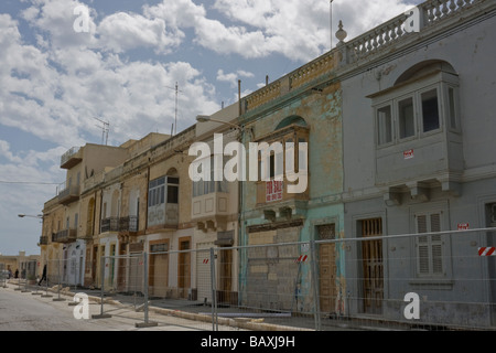 A street scene of houses covered in scaffolding and 'for sale' signs in the Maltese fishing village of Marsaxlokk, - Stock Photo