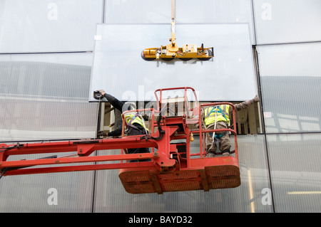 London Hackney May 2009 Installing large windows in new council building - Stock Photo