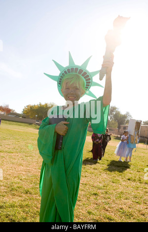 elementary school age girl dressed up in Statue of Liberty halloween costume, holding torch to sunlight - Stock Photo